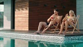 Pares alegres que se relajan en sillas del sol cerca de piscina en la casa de lujo almacen de video