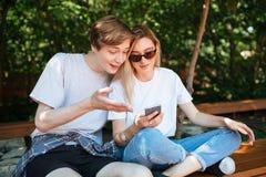 Pares alegres que se sientan en banco en parque y emocionalmente la discusión algo mientras que usa el teléfono móvil Ciérrese en Imágenes de archivo libres de regalías