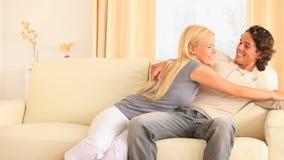Pares alegres que se sientan en un sofá que ve la TV el luchar para el telecontrol almacen de video