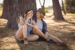 Pares alegres que se sientan por el tronco de árbol Fotografía de archivo