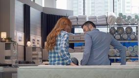 Pares alegres que sorriem à câmera, ao escolher a cama nova na loja de móveis video estoque