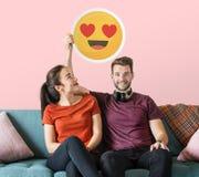 Pares alegres que sostienen un emoticon de los ojos del corazón foto de archivo libre de regalías
