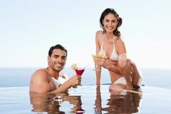 Pares alegres que tienen cocteles en la piscina Fotografía de archivo libre de regalías