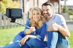 Pares alegres que tomam selfies com uma vara do selfie Foto de Stock Royalty Free