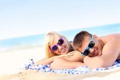 Pares alegres que toman el sol en la playa foto de archivo