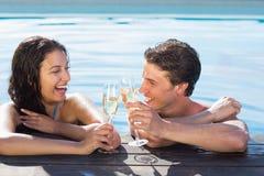 Pares alegres que tuestan el champán en piscina Fotos de archivo