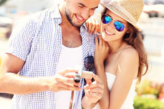 Pares alegres que verificam imagens na câmera Imagens de Stock Royalty Free