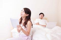 Pares alegres usando a almofada de toque na cama Fotografia de Stock
