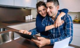 Pares alegres usando la tableta digital en el hogar de la cocina Fotografía de archivo