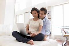 Pares alegres usando o portátil junto em casa Fotografia de Stock Royalty Free