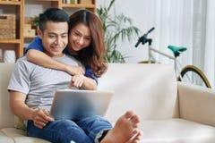 Pares alegres usando o portátil no sofá fotos de stock royalty free