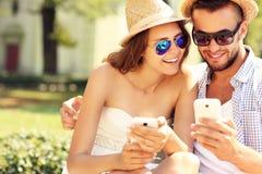 Pares alegres usando smartphones en el parque Imagen de archivo