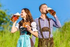 Pares alemanes en Tracht con la cerveza, pretzel Imagen de archivo libre de regalías