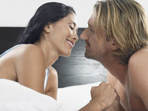 Pares alrededor a besarse en cama Imagenes de archivo