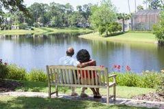 Pares americanos africanos superiores que sentam-se no banco de parque imagem de stock