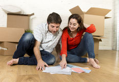 pares americanos felizes que sentam-se no assoalho que move-se na casa nova que olha modelos fotos de stock royalty free