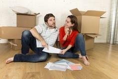 pares americanos felizes que sentam-se no assoalho que move-se na casa nova que olha modelos imagens de stock