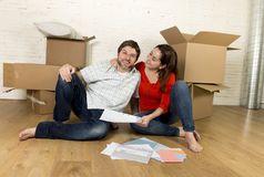 pares americanos felizes que sentam-se no assoalho que move-se na casa nova que olha modelos foto de stock