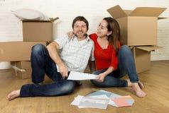 pares americanos felizes que sentam-se no assoalho que move-se na casa nova que olha modelos foto de stock royalty free