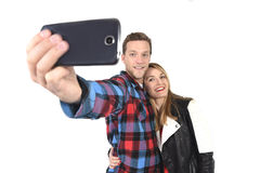Pares americanos hermosos jovenes en el amor que toma la foto romántica del selfie del autorretrato así como el teléfono móvil Fotografía de archivo libre de regalías