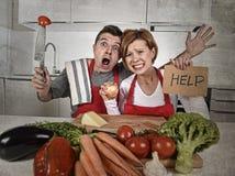 Pares americanos na cozinha do esforço em casa em cozinhar o avental que pede a ajuda frustrada imagem de stock
