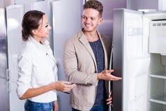 Pares amistosos jovenes que eligen el nuevo refrigerador en hipermercado Imágenes de archivo libres de regalías