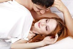 Pares amorosos felices atractivos jovenes en el dormitorio Fotos de archivo libres de regalías
