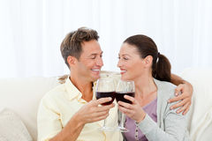 Pares apaixonado que bebem o vinho vermelho no sofá Fotografia de Stock Royalty Free