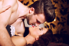Pares apaixonado que beijam na cama Imagem de Stock
