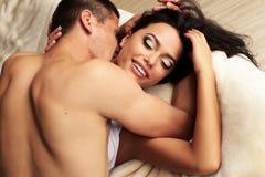 Pares apasionados atractivos que se besan en cama en el hotel Fotos de archivo