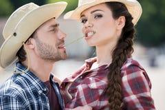 Pares apasionados del estilo del vaquero que abrazan con la paja Imagen de archivo