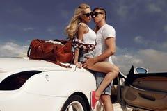 Pares apasionados en la ropa casual, presentando al lado del coche lujoso Imagenes de archivo