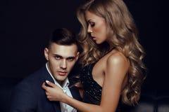 Pares apasionados hombres serios hermosos con la muchacha hermosa con el pelo rubio largo Foto de archivo libre de regalías