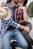 Pares apasionados que abrazan y que se besan mientras que se sienta en la cerca de madera Fotografía de archivo