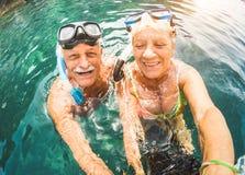Pares aposentados felizes que tomam o selfie na excursão tropical do mar foto de stock
