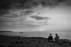 Pares aposentados na costa de relaxamento do por do sol Imagens de Stock Royalty Free