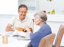 Pares aposentados que comem na cozinha imagem de stock royalty free