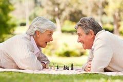 Pares aposentados que jogam a xadrez Fotografia de Stock