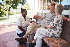 Pares aposentados que relaxam fora com cuidador fêmea Fotografia de Stock Royalty Free