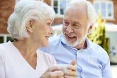 Pares aposentados que sentam-se no banco com bebida quente na facilidade viva ajudada foto de stock royalty free