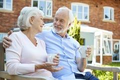 Pares aposentados que sentam-se no banco com bebida quente na facilidade viva ajudada imagem de stock royalty free