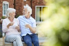 Pares aposentados que sentam-se no banco com bebida quente na facilidade viva ajudada fotos de stock