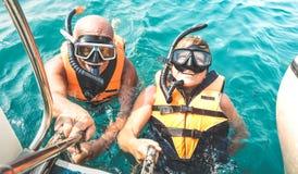 Pares aposentados que tomam o selfie feliz na excursão tropical do mar com vestes de vida e máscaras do tubo de respiração - merg imagens de stock royalty free