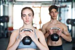 Pares aptos de los jóvenes en el gimnasio que ejercita con el kettlebell Imagen de archivo