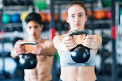 Pares aptos de los jóvenes en el gimnasio que ejercita con el kettlebell Foto de archivo