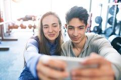 Pares aptos en gimnasio moderno del crossfit con smartphone Imagenes de archivo