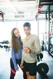 Pares aptos en gimnasio moderno del crossfit con smartphone Foto de archivo libre de regalías