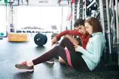 Pares aptos en gimnasio moderno del crossfit con smartphone Fotos de archivo