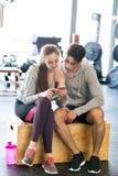 Pares aptos en gimnasio moderno del crossfit con smartphone Imagen de archivo