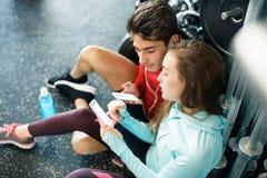 Pares aptos en gimnasio moderno del crossfit con smartphone Imagen de archivo libre de regalías